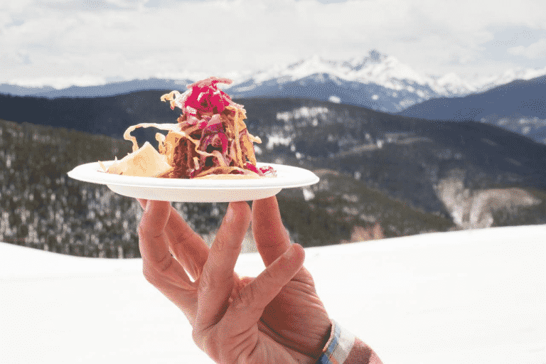 hand holding a plate with a luxury appetizer in front of snow topped mountains, symbolizing Enlightened Journeys Travel luxury travel services