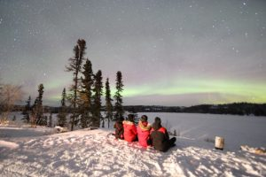 family who planned a luxury family trip, finally sitting in front of the Northern Lights