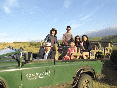 children, parents and grand parents on their multi family vacation, participating in a safari