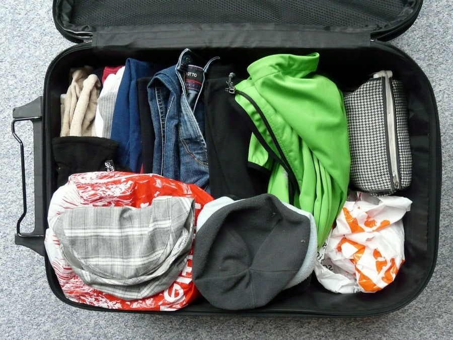open suitcase with cloth, jacket, shirts, hats, how to pack a suitcase for a sustainable and transformational vacation