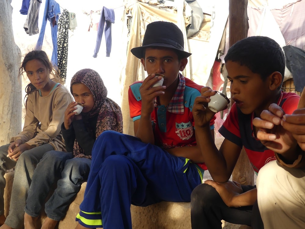 children drinking tea in a bedouin village in the desert in jordan, visited by luxury travel advisor Theresa Jackson