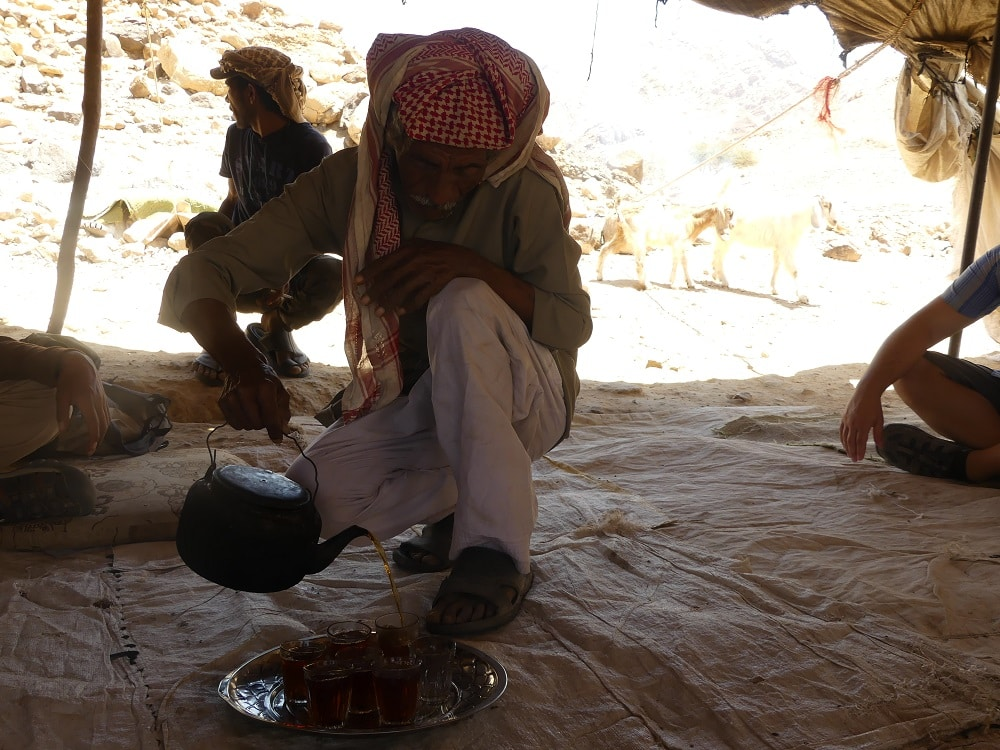 cooking tea underneath a tent in a bedouin village in jordan, visited by luxury travel advisor Theresa Jackson