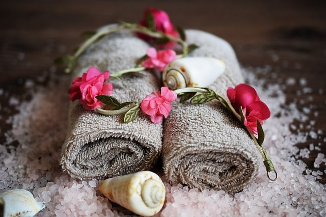 pink flowers, sea shells, sea salt, and massage towels, symbolizing the beauty and wellness at top spa destinations europe