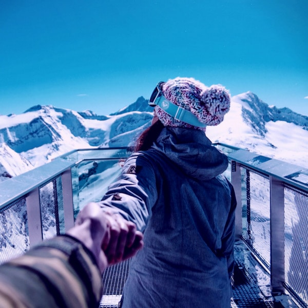woman in winter outfit, holding her partner's hand and pulling him forward, surrounded by snow, luxury group travel planned by Enlightened Journeys Travel