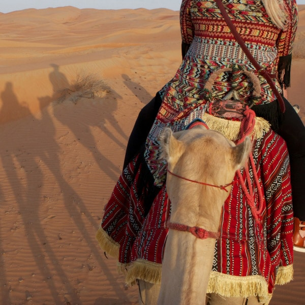 woman riding on a camel in the dessert, luxury solo and single travel, planned by Enlightened Journeys Travel