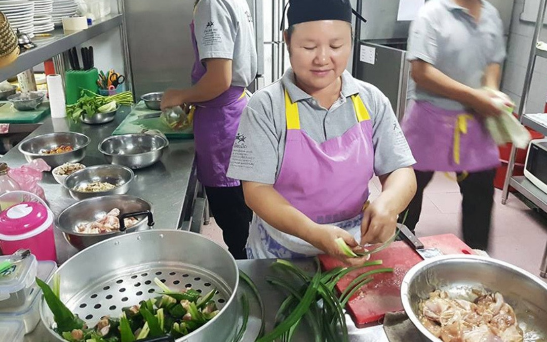 women in a restaurant kitchen preparing food for their restaurant guests, Eat with A Purpose - How Your Best Travel Experiences Can Make the World Better For Others