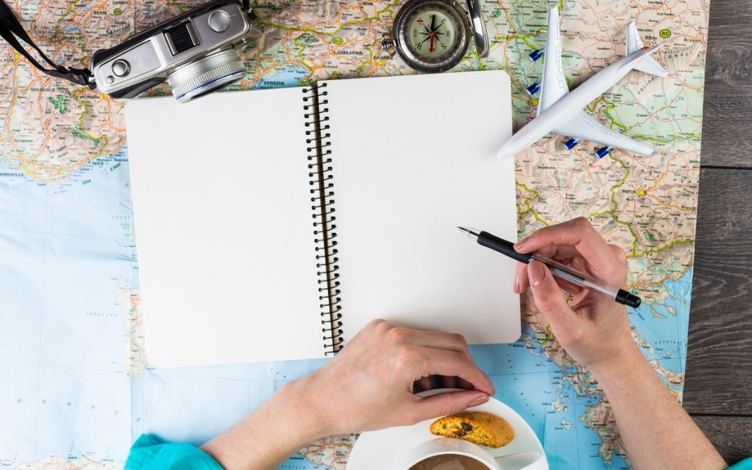woman has her notebook in front of her, pen in her hand and is eating pastries and drinking coffee, How a Comedy Technique Can Help You Have Extraordinary Travel Adventures