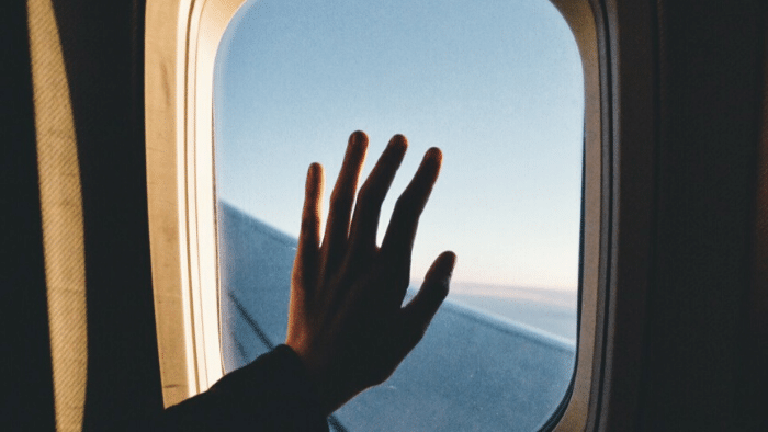 in an airplane, hand on the window
