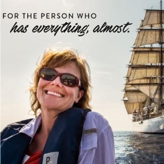 woman in front of sailboat, Virtuoso Wanderlist specialist Theresa Jackson of Enlightened Journeys Travel