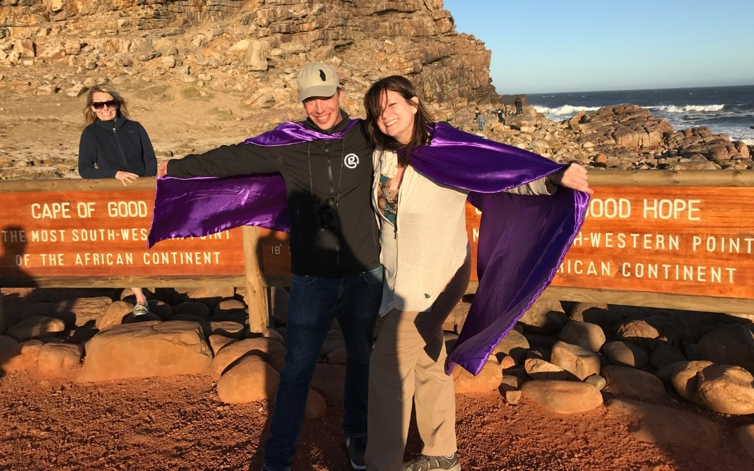 Two luxury travelers in front of the sign Cape of Good Hope, the most south-west point of the African continent, what is sustainable tourism